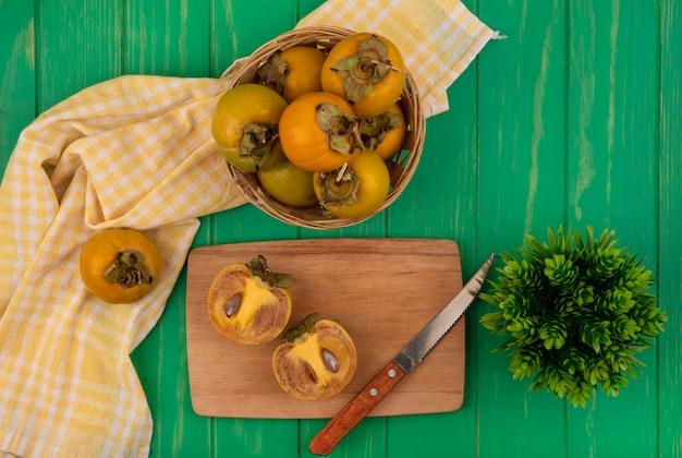 Bovenaanzicht van oranje ronde kaki vruchten op een emmer met gehalveerde kaki vruchten op een houten keukenplank met mes op een groene houten tafel