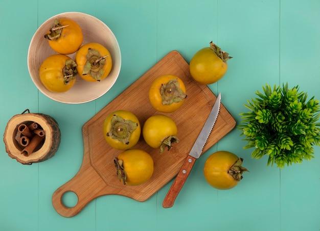 Bovenaanzicht van oranje ronde kaki vruchten op een houten keuken bord met mes kaneelstokjes op een houten pot op een blauwe houten tafel