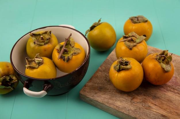Bovenaanzicht van oranje ronde kaki vruchten op een houten keukenplank met kaki vruchten op een kom op een blauwe houten tafel
