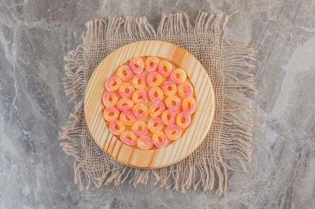 Bovenaanzicht van oranje snoepjes in ringvorm op houten plaat over zak.