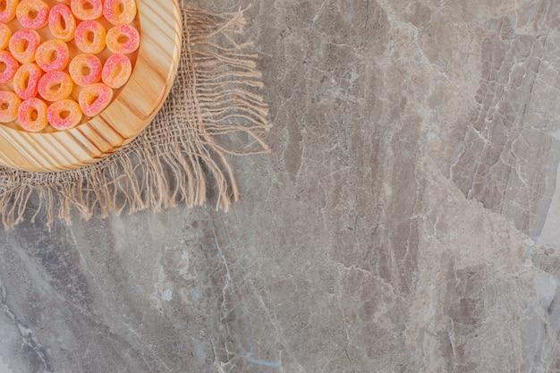 Bovenaanzicht van oranje snoepjes in ringvorm over houten plaat.