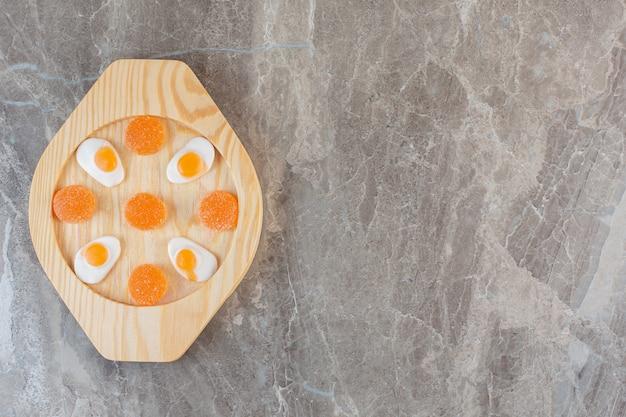 Bovenaanzicht van oranje snoepjes op houten plaat.