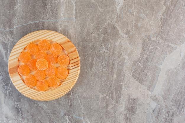 Bovenaanzicht van oranje zoete snoepjes op een houten bord over grijze achtergrond.
