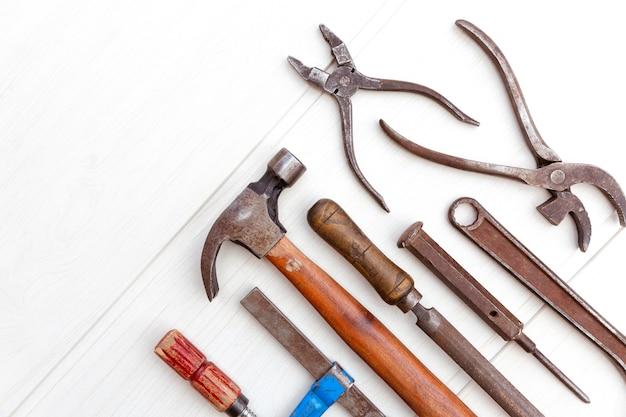 Bovenaanzicht van oude en roestige toolset op lichtgekleurde houten bord. diy-concept.
