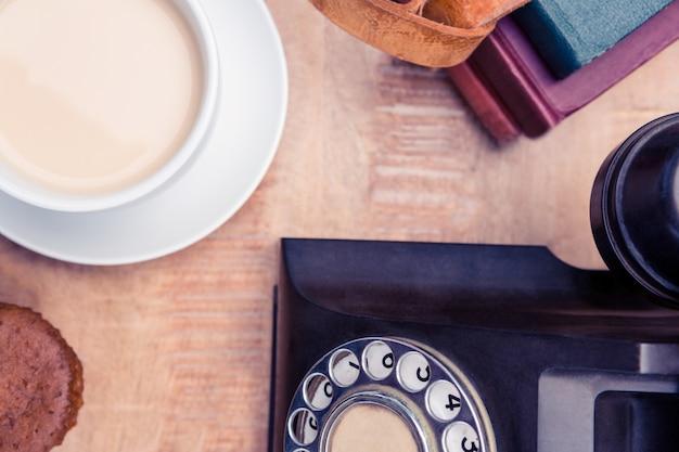 Bovenaanzicht van oude vaste telefoon met dagboeken en koffie op tafel