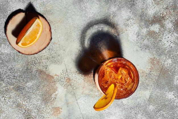 Bovenaanzicht van ouderwetse cocktail met sterk gericht licht dat harde schaduw vormt