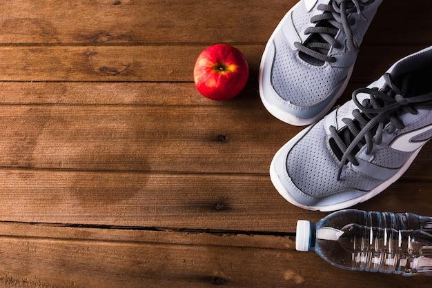 Bovenaanzicht van paar sportschoenen fles water en rode appel