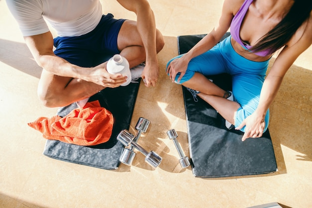Bovenaanzicht van paar zittend op de matten met gekruiste benen en rust van de training. man met fles met water. gym interieur.