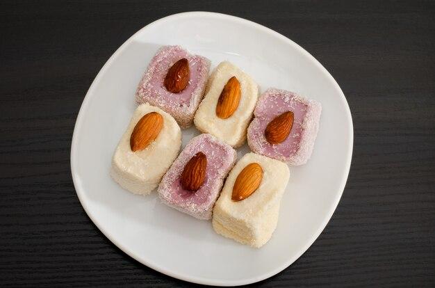Bovenaanzicht van paars en wit turks fruit met amandelen, zwarte tafel
