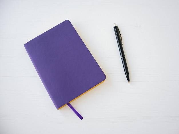 Bovenaanzicht van paarse notitieboekjedekking met pen.