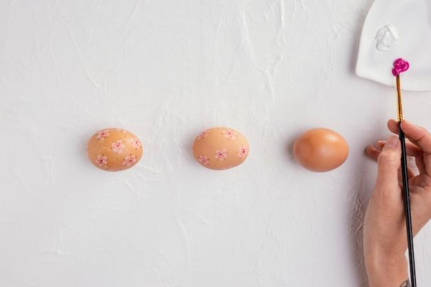 Bovenaanzicht van paaseieren met penseel van de handholding
