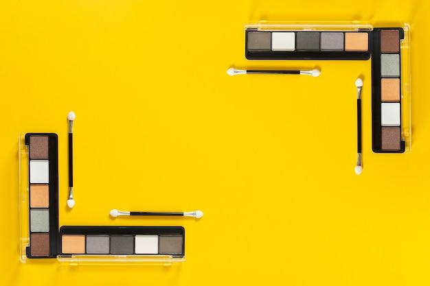 Bovenaanzicht van paletten op gele achtergrond met kopie ruimte