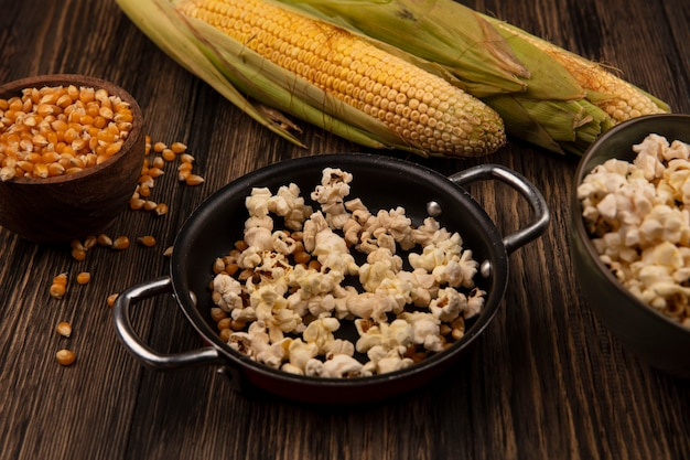 Bovenaanzicht van pan met popcorn met maïskorrels met verse likdoorns geïsoleerd op een houten kom op een houten tafel