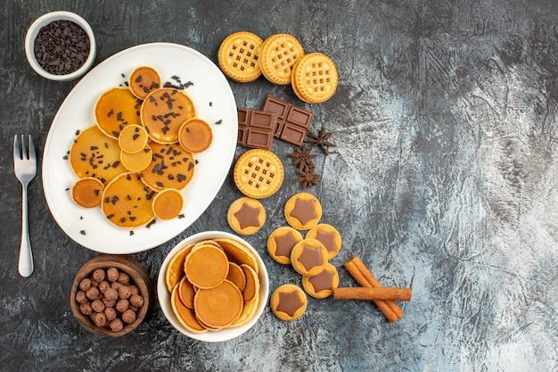 Bovenaanzicht van pannenkoeken en verschillende soorten desserts op grijze achtergrond