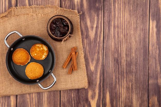 Bovenaanzicht van pannenkoeken in pan en pot aardbeienjam met kaneel op zak op houten achtergrond met kopie ruimte
