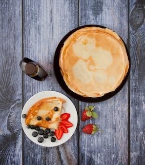 Bovenaanzicht van pannenkoeken met bessen en stroop