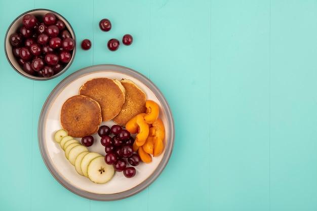 Bovenaanzicht van pannenkoeken met gesneden abrikoos en peer en kersen in plaat met kom met kersen op blauwe achtergrond met kopie ruimte
