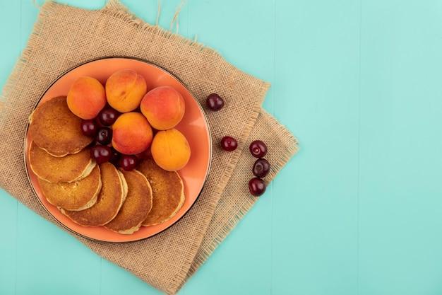 Bovenaanzicht van pannenkoeken met kersen en abrikozen in plaat op zak op blauwe achtergrond met kopie ruimte