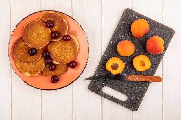 Bovenaanzicht van pannenkoeken met kersen in plaat en abrikozen met mes op snijplank op houten achtergrond