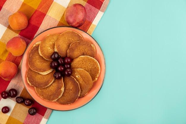 Bovenaanzicht van pannenkoeken met kersen in plaat en abrikozen op geruite doek op blauwe achtergrond met kopie ruimte