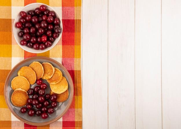 Bovenaanzicht van pannenkoeken met kersen in plaat en kom met kersen op geruite doek en houten achtergrond met kopie ruimte