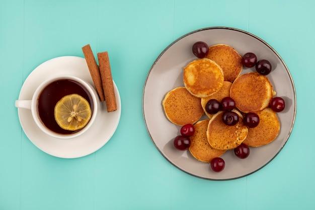 Bovenaanzicht van pannenkoeken met kersen in plaat en kopje thee met schijfje citroen erin en kaneel op schotel op blauwe achtergrond