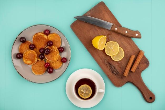 Bovenaanzicht van pannenkoeken met kersen in plaat en kopje thee met schijfjes citroen en kaneel met mes op snijplank op blauwe achtergrond