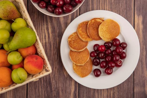 Bovenaanzicht van pannenkoeken met kersen in plaat en mand met fruit als peren-abrikozenpruim op houten achtergrond