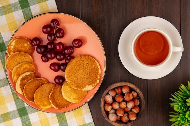 Bovenaanzicht van pannenkoeken met kersen in plaat op geruite doek en kom met noten met kopje thee op houten achtergrond