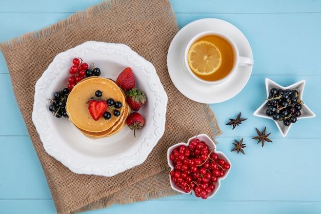 Bovenaanzicht van pannenkoeken met rode en zwarte bessen en aardbeien met een kopje thee op een blauwe ondergrond