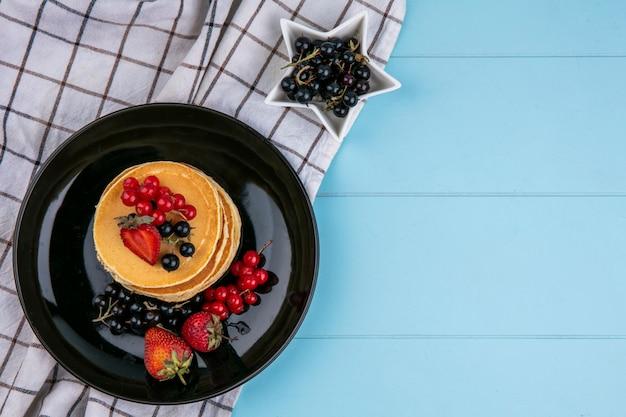 Bovenaanzicht van pannenkoeken met rode en zwarte bessen en aardbeien op een zwarte plaat op een blauw oppervlak