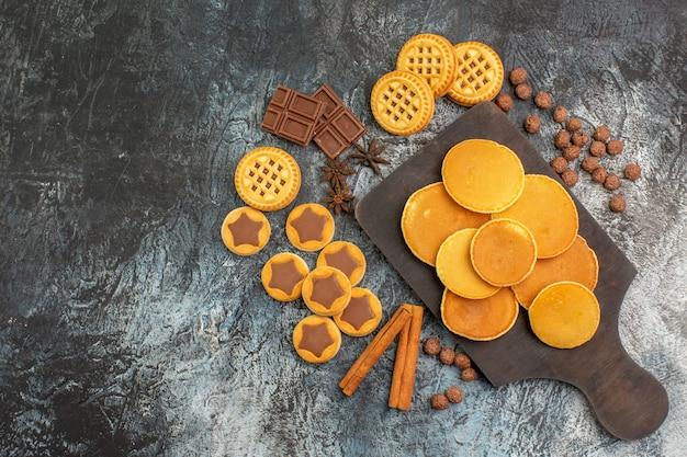 Bovenaanzicht van pannenkoeken op houten schotel met koekjes en snoep op grijze grond