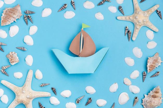 Bovenaanzicht van papier boot met zeester en zeeschelpen