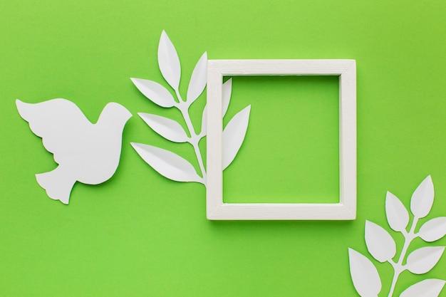Bovenaanzicht van papier duif met frame en bladeren