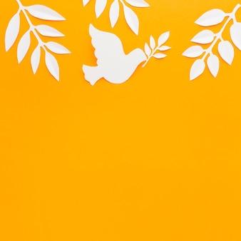 Bovenaanzicht van papier duif met kopie ruimte en papieren bladeren