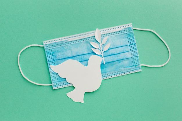 Bovenaanzicht van papier duif met medische masker