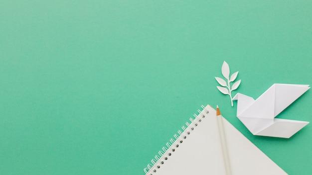 Bovenaanzicht van papier duif met notebook en bladeren