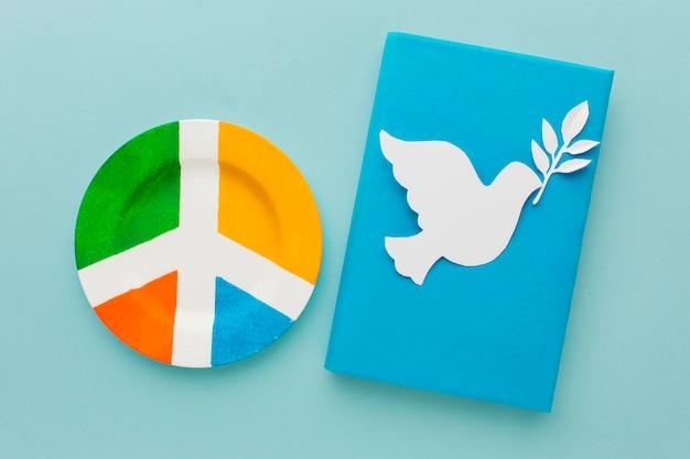Bovenaanzicht van papier duif met vredesteken plaat