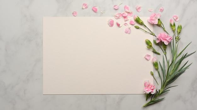 Bovenaanzicht van papier en roze bloem versierd op marmeren bureau