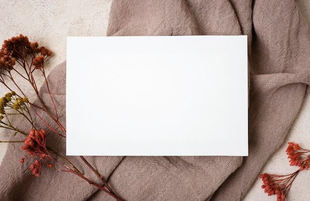 Bovenaanzicht van papier met herfst plant en stof