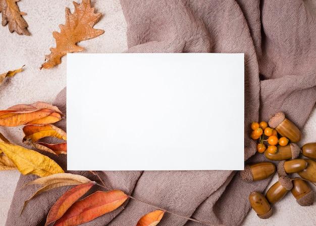Bovenaanzicht van papier met herfstbladeren en eikels