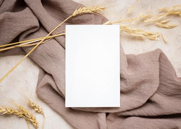 Bovenaanzicht van papier met herfstplant en textiel
