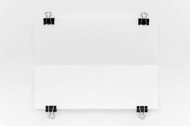 Bovenaanzicht van papier met metalen clips op hoeken