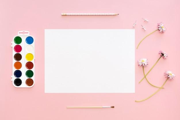Bovenaanzicht van papier met palet en bloemen