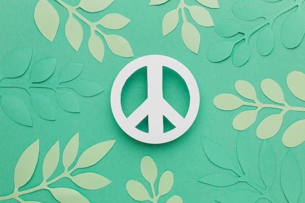 Bovenaanzicht van papier vredesteken met bladeren