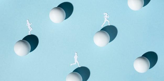 Bovenaanzicht van papieren atleten met pingpongballen