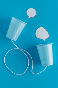 Bovenaanzicht van papieren bekers met touwtje en praatjebellen