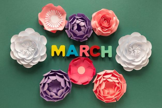 Bovenaanzicht van papieren bloemen met maand voor vrouwendag