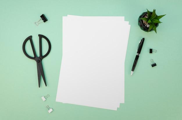 Bovenaanzicht van papieren en schaar op bureau