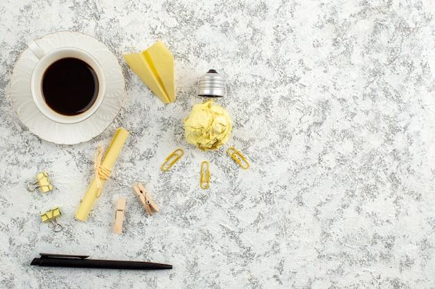 Bovenaanzicht van papieren gloeilamp papieren vliegtuigpen een kopje zwarte thee op een witte ondergrond